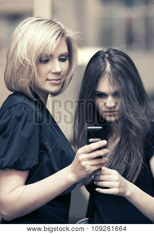 Two young fashion women looking at mobile phone in office