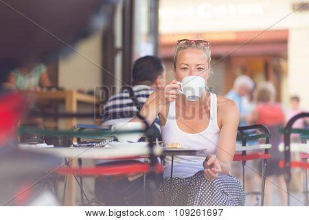 Woman drinking coffee outdoor on street.