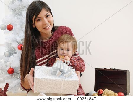 Portrait Of Happy Smiling Mother And Her Baby Near Christmas Tree