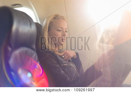 Woman reading newspaper on airplane.