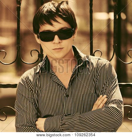 Young handsome man in sunglasses at the cast iron fence