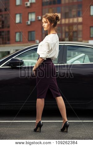 Young fashion business woman on the city street next to her car