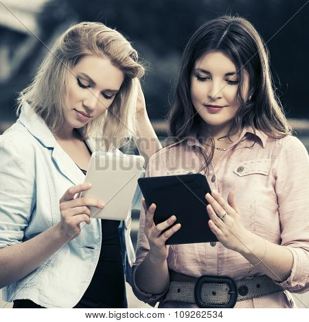 Two young fashion women with a digital tablet computers