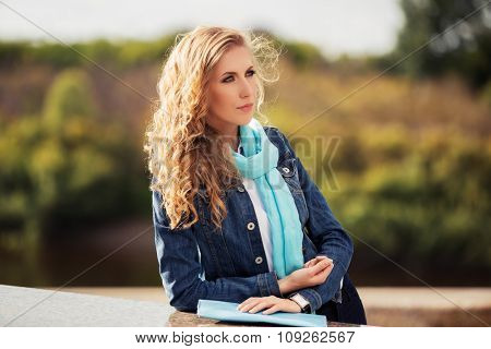 Young fashion blond woman walking on the city street