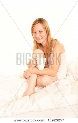 Young Woman In Nightdress Drinking Coffee In Bed