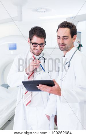 Doctors discussing images of x-ray scan standing in front of CT machine in hospital