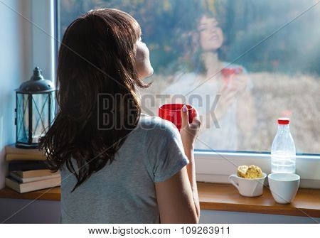 Young  woman holding cup of coffee sitting home by the window. Face reflection on the glass