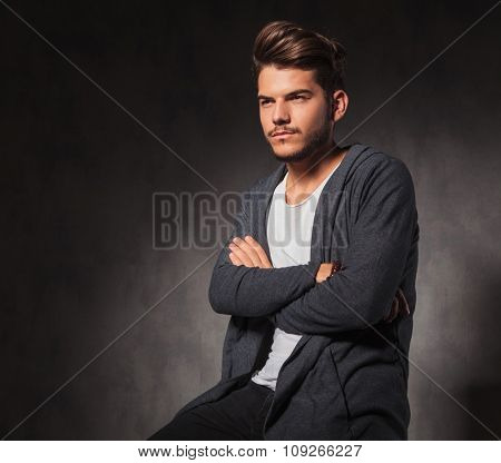 portrait of man in studio with hands crossed looking away from the camera