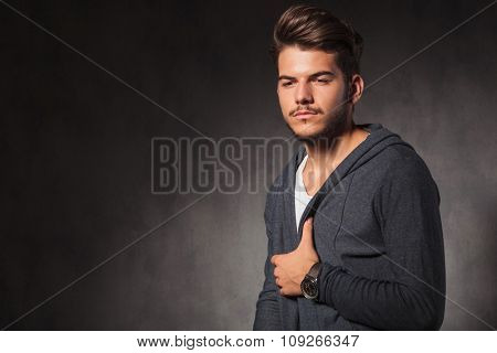 portrait of young man looking down arranging his jacket while posing in studio background