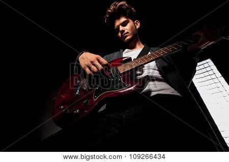 cool young artist in dark backgroud playing guitar while looking down