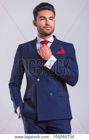 elegant man in business suit posing in studio with hand in pocket while fixing his tie