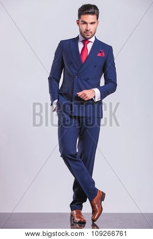 full body portrait of handsome business man posing standing legs crossed with hand in pocket