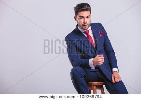 elegant corporate man leaning on a chair while sitting in studio