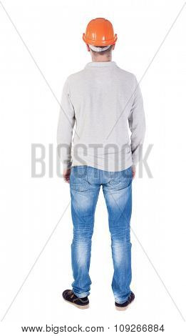 Backview of an engineer in construction helmet stands. Standing young guy. Rear view people collection.  backside view of person.  Isolated over white background.