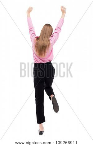 Back view of  business woman.  Raised his fist up in victory sign.    Isolated over white background. The girl office worker in black trousers held up her hands and legs.