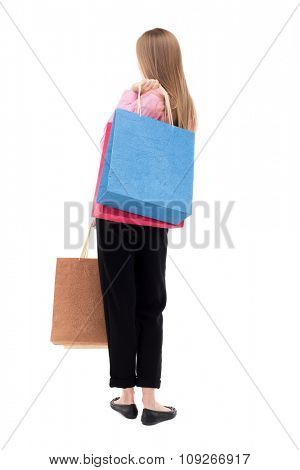 back view of woman with shopping bags . beautiful brunette girl in motion.  backside view of person.  Isolated over white background. girl in pink shirt is throwing shoulder bag with purchases.