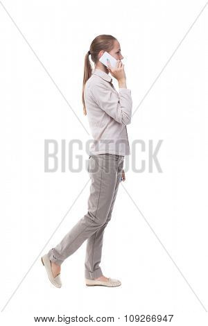 side view of a woman walking with a mobile phone. back view ofgirl in motion.  backside view of person.  Isolated over white background. A girl in a white jacket is talking on the white phone.