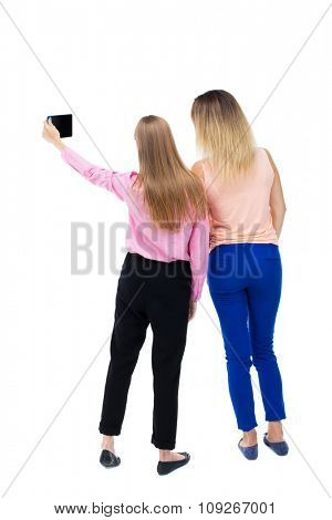 Back view of two young woman photographed on a mobile phone. Rear view people collection.  backside view of person. Rear view. Isolated over white background. Two girls blonde doing self smartphone.