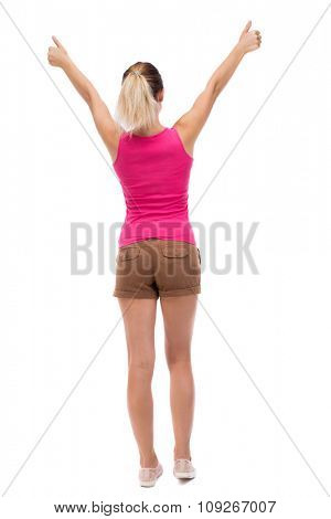 Back view of  woman thumbs up. Rear view people collection. backside view of person. Isolated over white background. Blonde in brown shorts showing thumbs up with both hands.