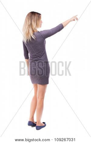 Back view of  pointing woman. beautiful girl. Rear view people collection.  backside view of person.  Isolated over white background. Girl in a short dress showing right hand.