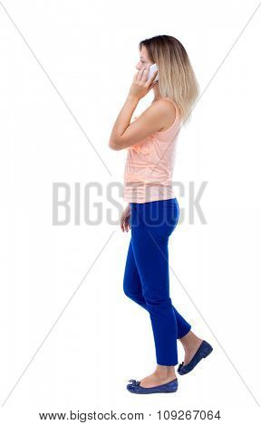 side view of a woman walking with a mobile phone. back view ofgirl in motion.  backside view of person.  Isolated over white background. Blonde in blue trousers is left talking on the white phone.