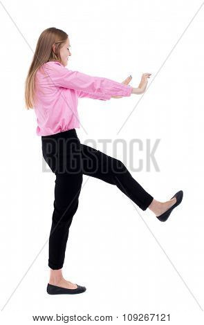 back view of business woman pushes wall.  Isolated over white background. Rear view people collection. backside view of person. Woman office worker in a pink shirt repels someone hands and feet.