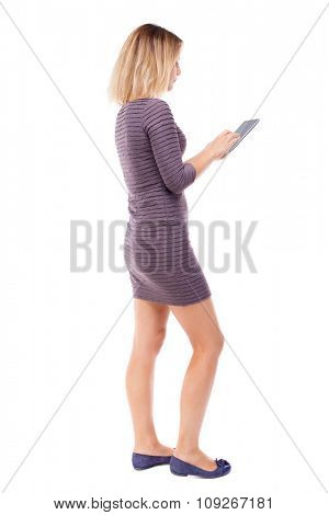 back view of standing young beautiful  girl with tablet computer in the hands of. girl  watching.   Isolated over white background. Girl in short dress stands sideways and writes in a Tablet PC.