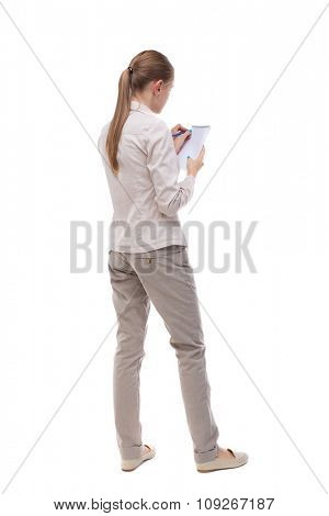 back view stands woman takes notes in notebook. girl watching. Rear view people collection. backside view person. Isolated over white. Girl with long hair in white jacket writing in notebook