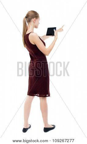back view of pointing young beautiful  girl with tablet computer. girl  watching. Isolated over white background.  blonde burgundy dress holding to a horizontal smartphone  and points in front of him.