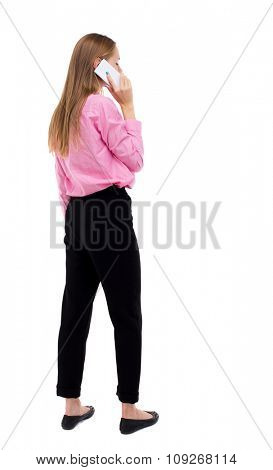 back view of woman talking on the phone.  backside view of person.  Rear view people collection. Isolated over white background. girl office worker in black trousers talking on smartphone looks right.