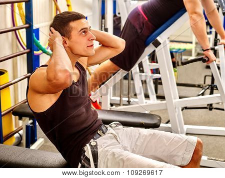 Man working his abdominal crunches on bench in gym.