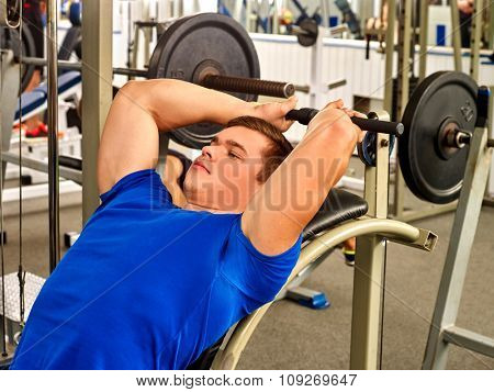 Man lying on bench working his arms and back at gym. He lying on bench and lifting barbell.