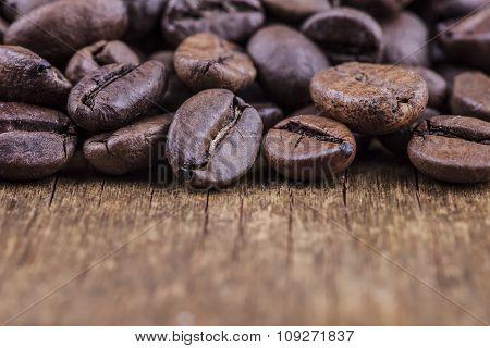 coffee grains on grunge wooden background closeup
