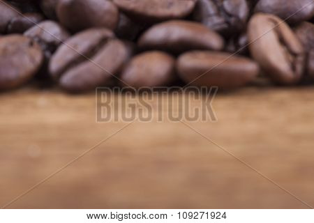 blurred image. coffee grains on grunge wooden background