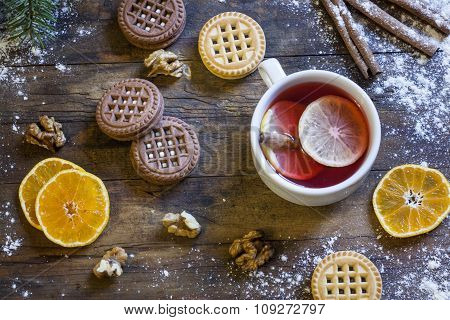 Tea, tangerines and cookies in Christmas decor with Christmas tree, nuts and apples on dark wooden b