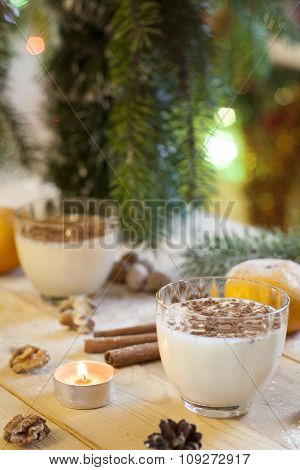 Vanilla panna cotta with chocolate, tangerines, cones, cinnamon and nuts in Christmas decor