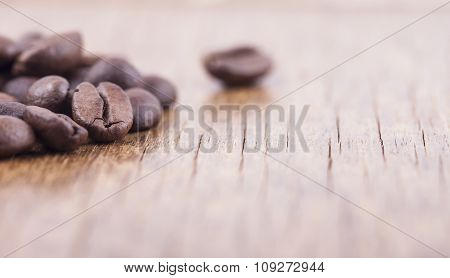 coffee grains on wooden background closeup