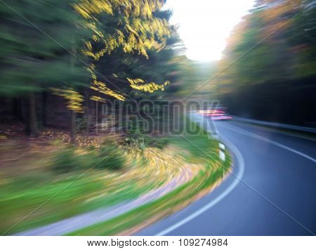 Road  through wood with artistic motion blur - turning left