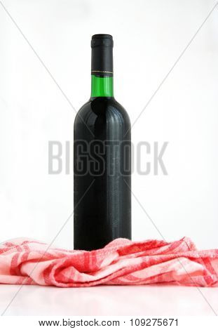 Isolated red wine bottle with red cloth out of focus. Cold red wine - condensation on the bottle