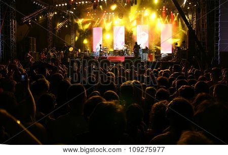 Rock music band playing on a concert stage.