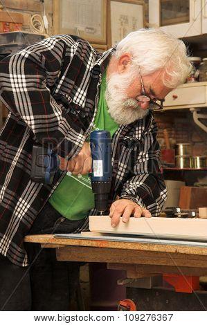Old man working. Old man with grey beard making something
