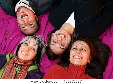 Young Women friends and a young man smile. Happy Friends laying together smiling
