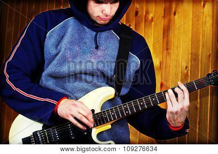 Guitarist play rock guitar. White eletric guitar