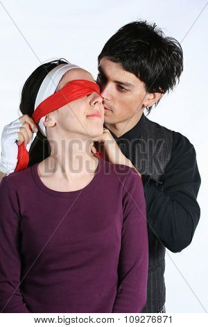 Man putting red blindfold on woman eyes. Happy love couple game
