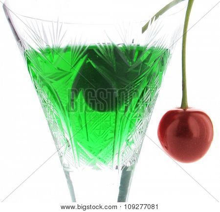 Acid green cocktail in glass with a red cherry. Sweet poison concept