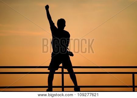 Silhouette of jumping man. victory concept. Happy man with raised hand