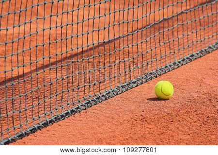 Detail of clay tennis court. Tennis ball and net detail