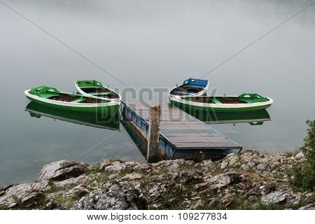 Boats on misty lake in morning. Nature concept