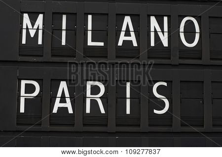 Flights info board on airport concept. Fashion cities Paris and Milan