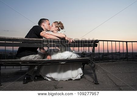 Happy, just married couple kissing outdoor at sunset. Wedding and marriage concept